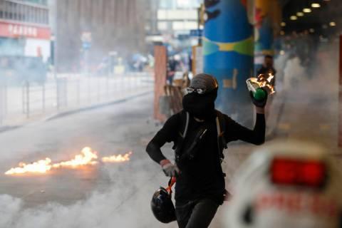 A protestor prepares to throw molotov cocktail in Hong Kong, Sunday, Sept. 29, 2019. Riot polic ...