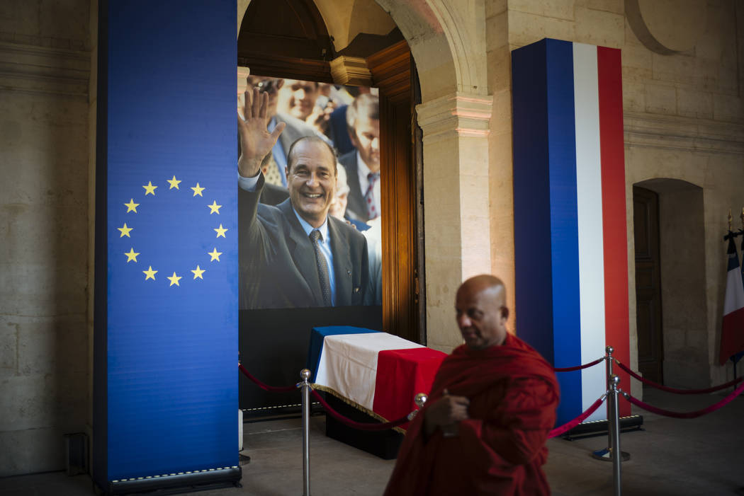 A monk walks past by the coffin of late French President Jacques Chirac, Sunday, Sept. 29, 2019 ...