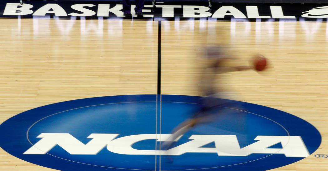 FILE - In this March 14, 2012, file photo, a player runs across the NCAA logo during practice a ...