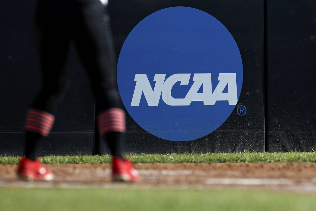 FILE - In this April 19, 2019, file photo, an athlete stands near a NCAA logo during a softball ...