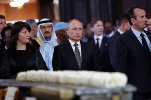 Russian President Vladimir Putin, center, stands before a service for late French President Jac ...