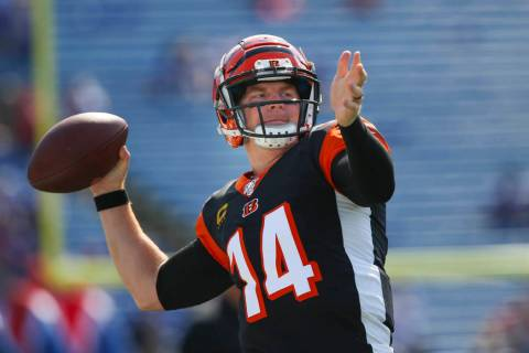 Cincinnati Bengals quarterback Andy Dalton (14) triple playas he warms up before a NFL football ...
