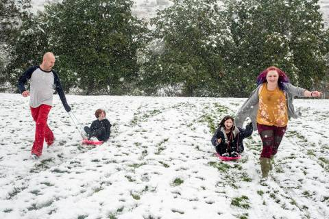 Tommy Little, from left, Cody Little, Kyndra Neal and Tanya Little use the snow accumulation to ...