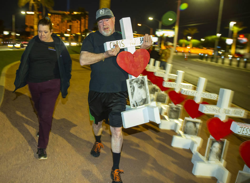 Michael and Leah Tuckman carry away a cross for Chris Roybal which they will present to his mot ...