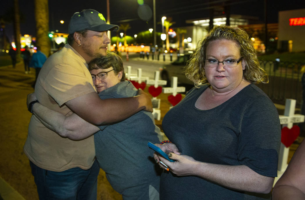 Devin Gray hugs Rosemary Semon with Heather Semon as Greg Zanis has placed 58 crosses near the ...