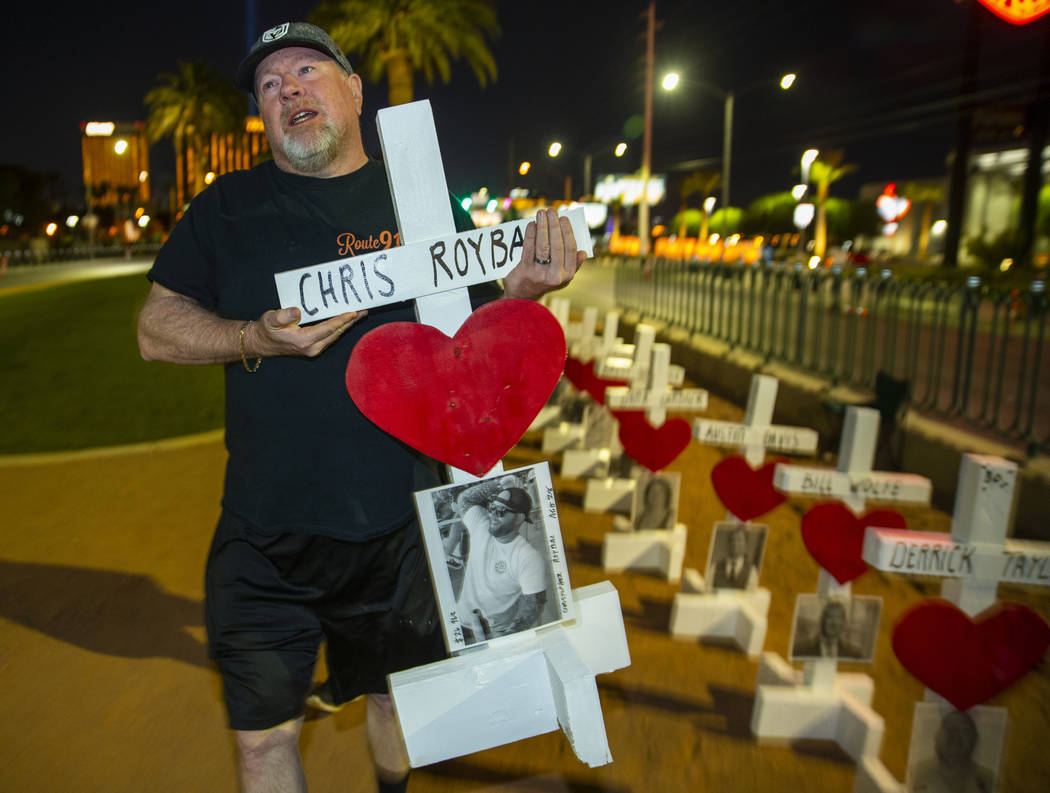 Michael Tuckman carries away a cross for Chris Roybal which they will present to his mother Deb ...