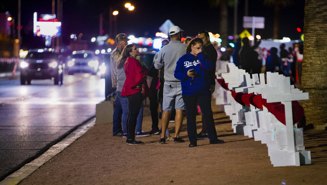 "Visitors walk along the line of 58 crosses Greg Zanis placed near the ""Welcome to Fabulous Las ..."