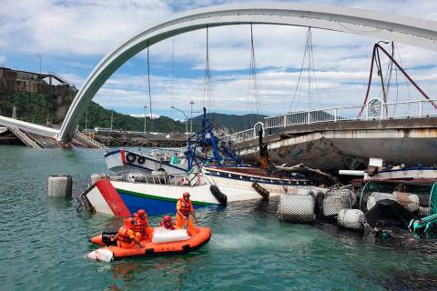 Rescuers work near the site of a collapsed bridge in Nanfangao, eastern Taiwan. Tuesday, Oct. 1 ...
