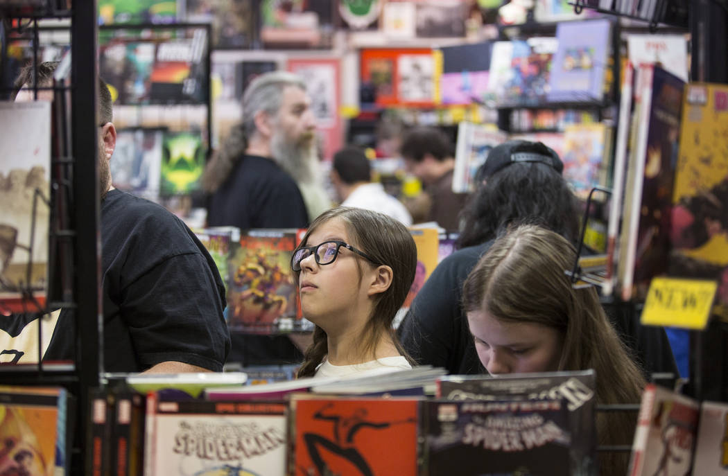 Shoppers peruse the aisles at Alternate Reality Comics during free comic book day at on Saturda ...