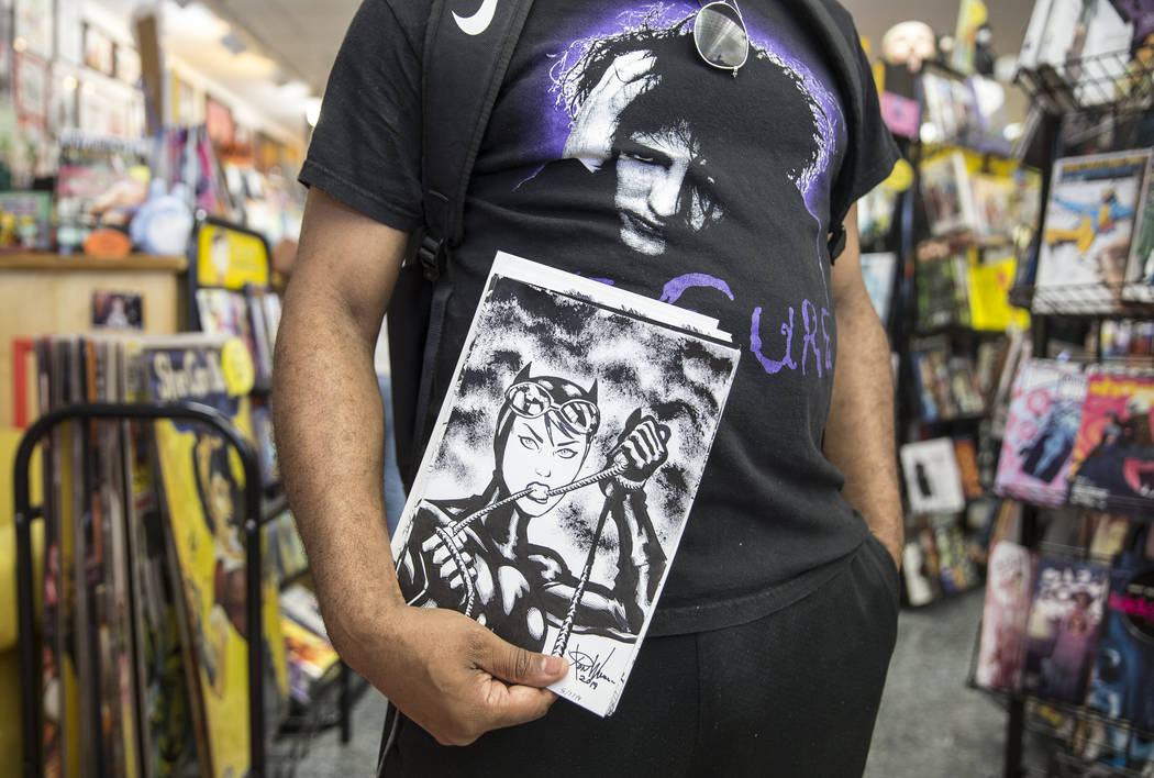 Comic book illustrator Ron Williams holds a sketch of Catwoman during free comic book day at Al ...