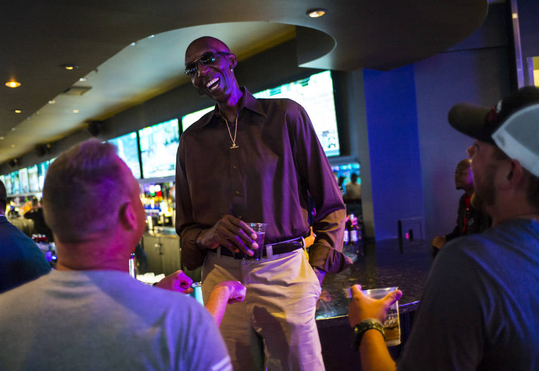 """George Bell, who stands 7'8"""", talks with tourists while hanging out at the Longbar at The ..."""