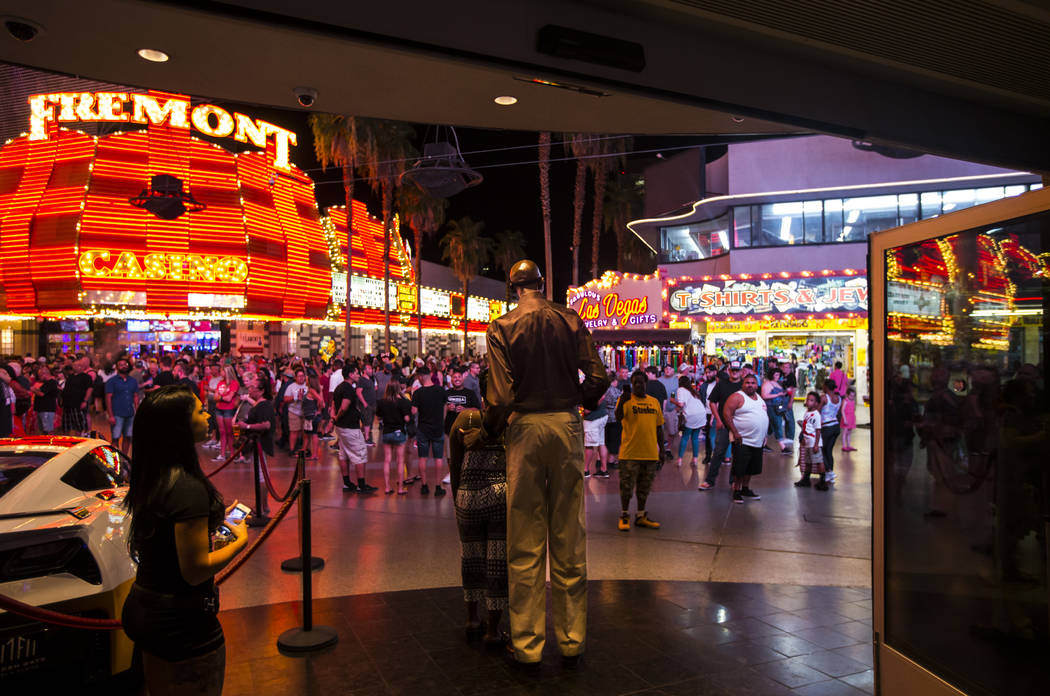 """George Bell, who stands 7'8"""", poses for pictures on the Fremont Street Experience outside ..."""