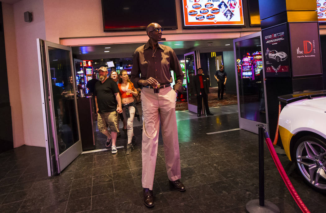 """George Bell, who stands 7'8"""", walks outside of The D Las Vegas to the Fremont Street Exper ..."""