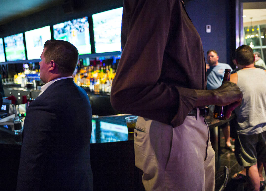 """George Bell, who stands 7'8"""", holds a beer while hanging out at the Longbar at The D Las V ..."""