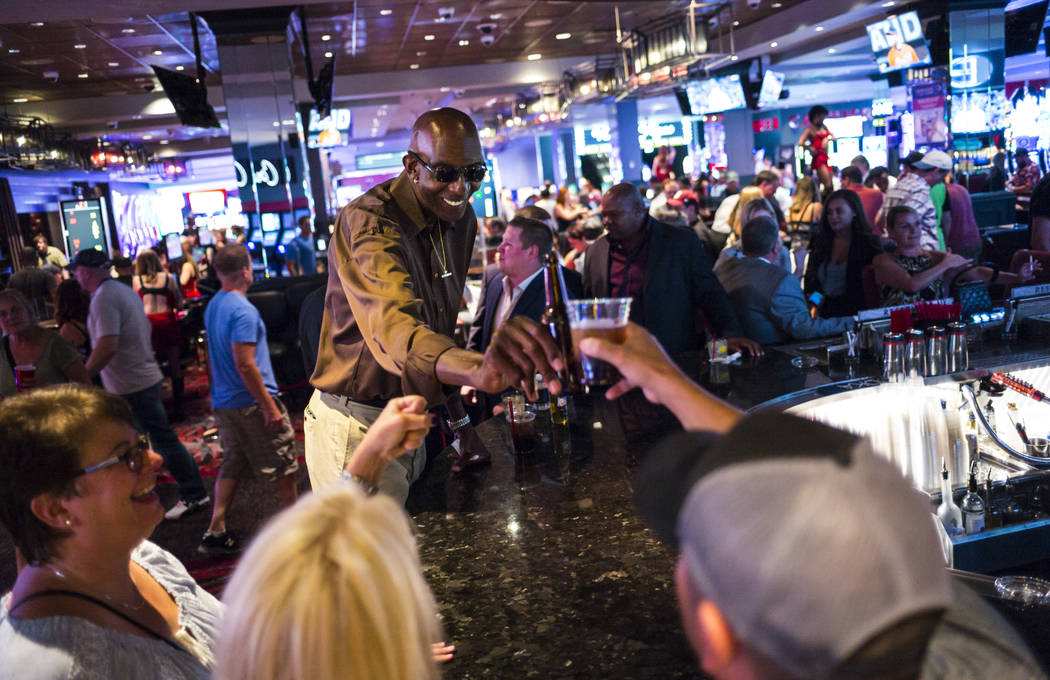 """George Bell, who stands 7'8"""", mingles with people while hanging out at the Longbar at The ..."""