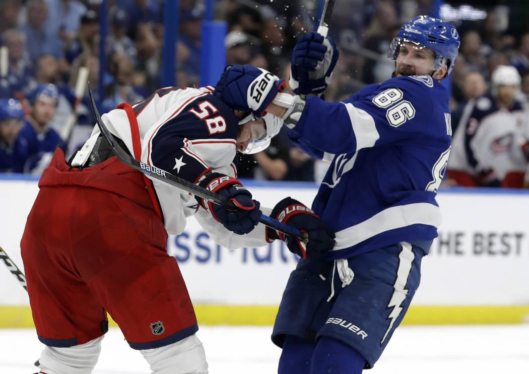 Tampa Bay Lightning right wing Nikita Kucherov (86) grabs Columbus Blue Jackets defenseman Davi ...