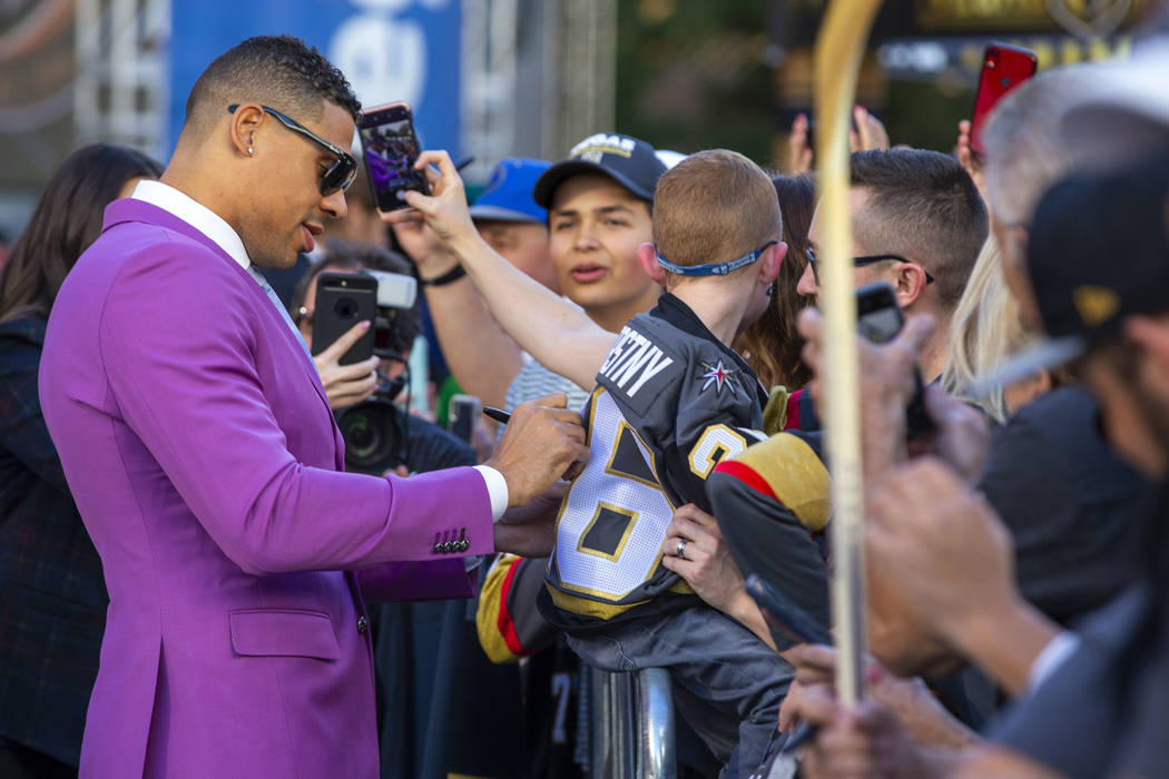 Vegas Golden Knights right wing Ryan Reaves signs an autograph for a fan while walking the gold ...