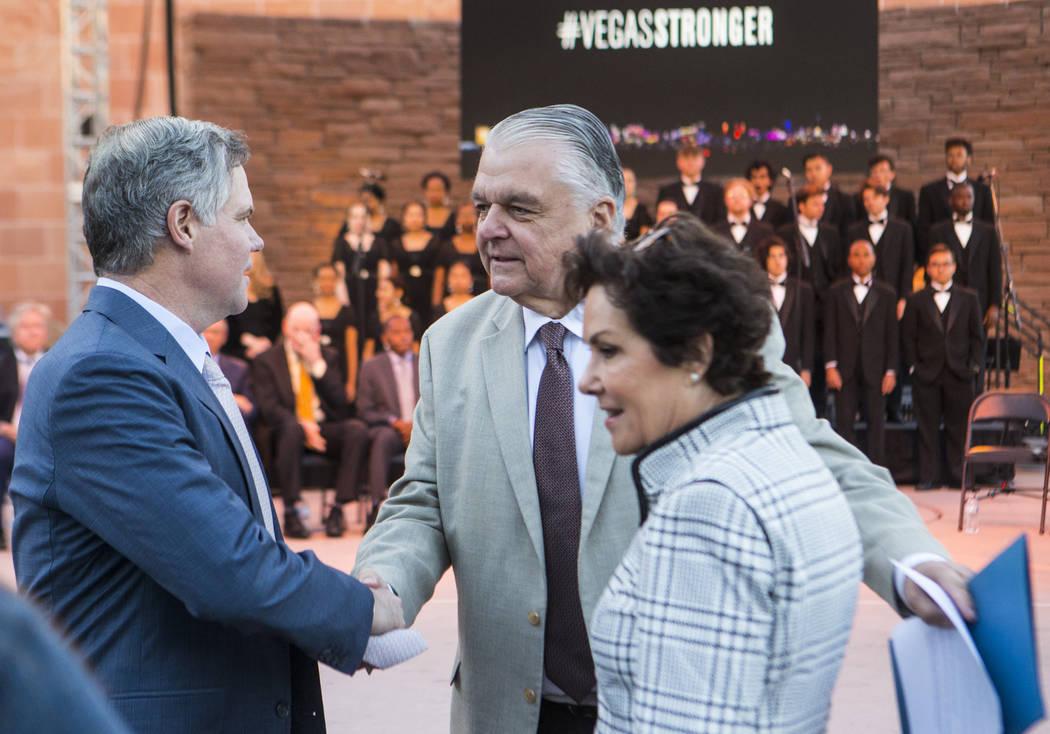Gov. Steve Sisolak, center, greets MGM Resorts International CEO Jim Murren, left, and U.S. Sen ...