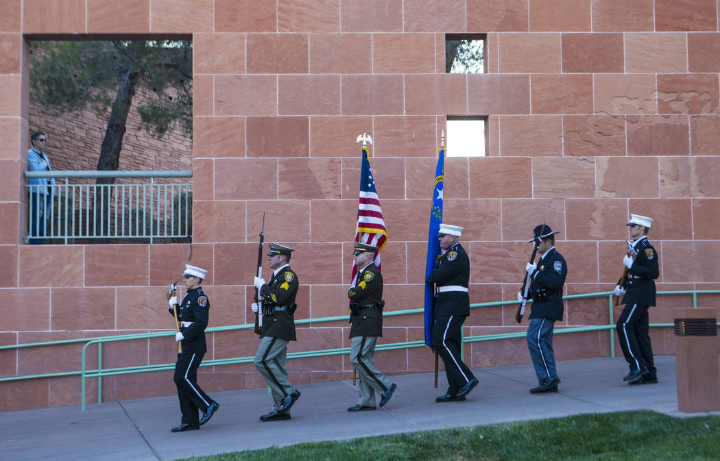 Members of a multi-agency honor guard march to present the colors during a sunrise ceremony in ...