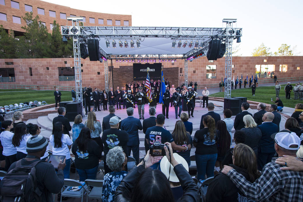 Attendees watch members of a multi-agency honor guard at the end of a sunrise ceremony in remem ...