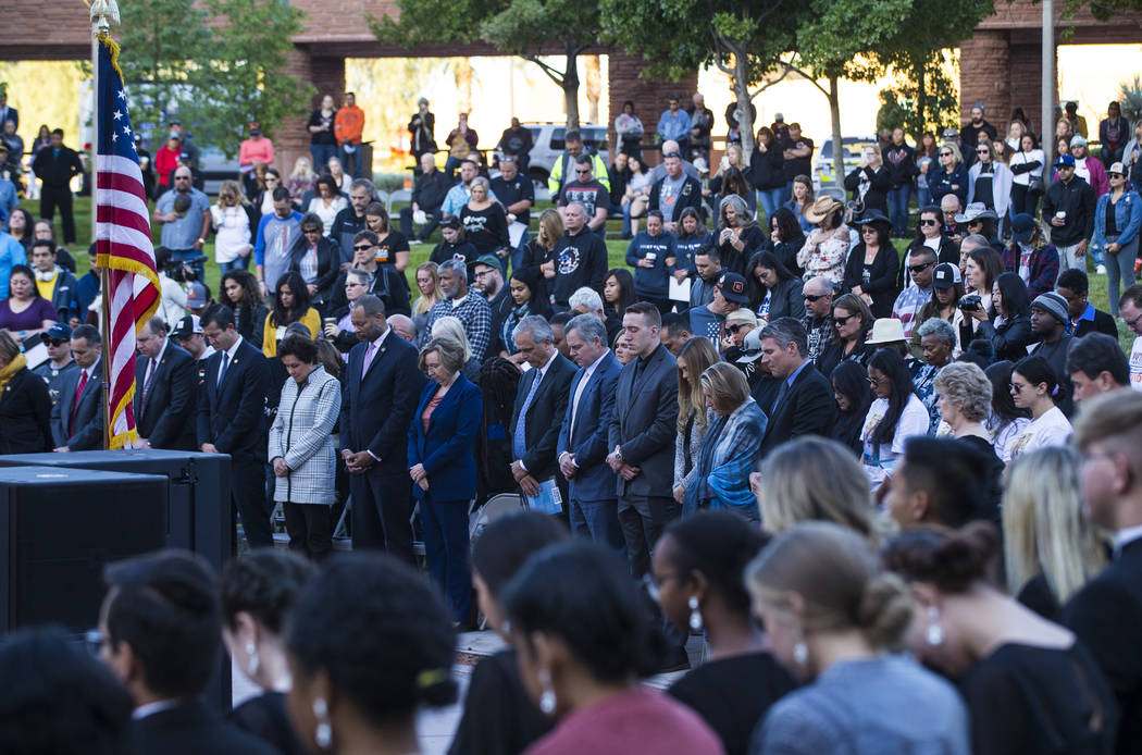 Attendees observe a moment of silence during a sunrise ceremony in remembrance of the 58 victim ...