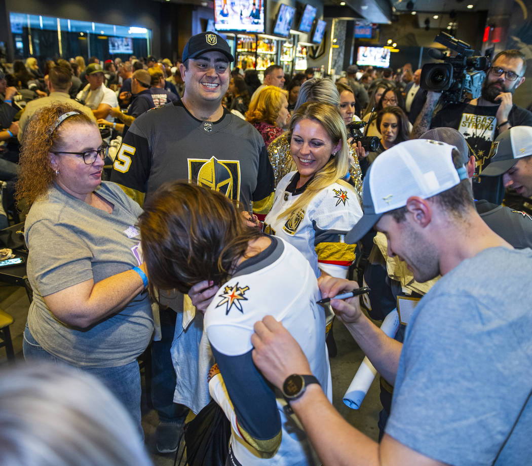 The Vegas Golden Knights Brayden McNabb, right, signs an autograph during a meet and greet to h ...