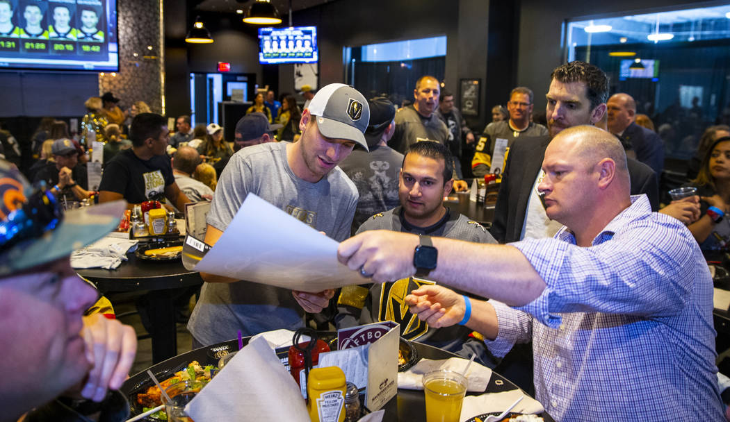 The Vegas Golden Knights Shea Theodore, center, signs an autograph during a meet and greet to h ...