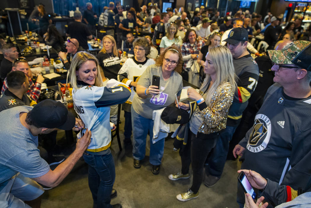 The Vegas Golden Knights Deryk Engelland, left, signs an autograph for Leslie Shaffer with Amer ...