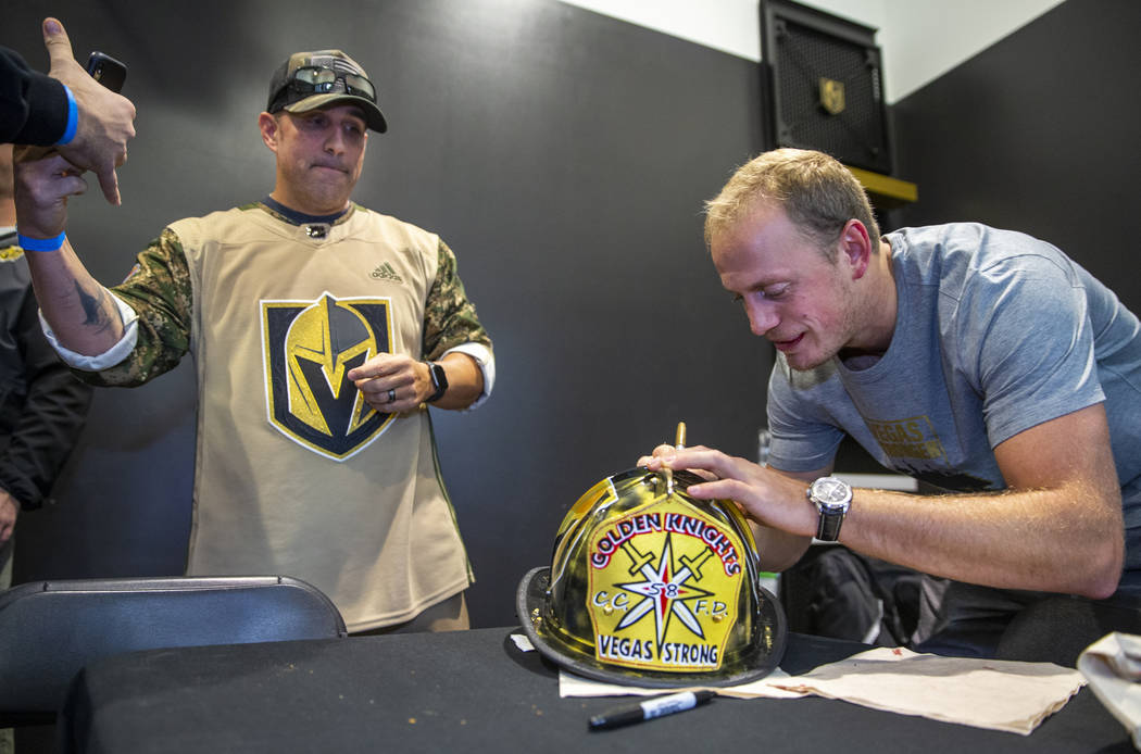 The Vegas Golden Knights Nate Schmidt, right, signs an autograph for Clark County firefighter C ...