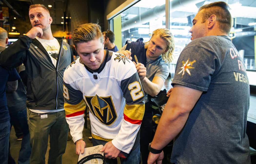 The Vegas Golden Knights William Karlsson, right, signs an autograph for Matt Sambol during a m ...