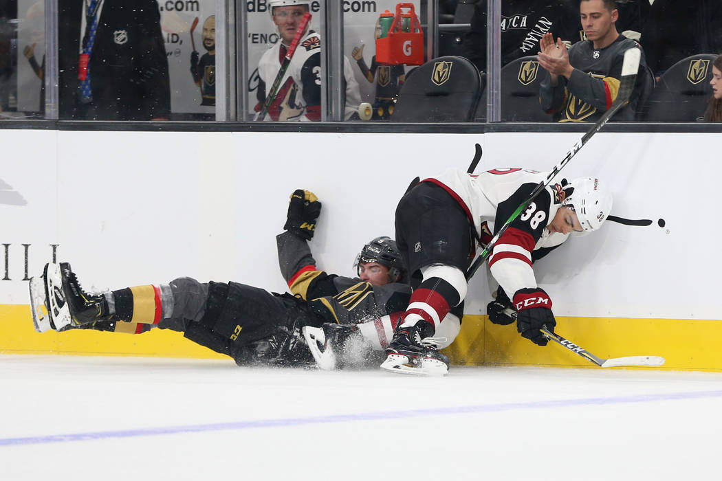 Vegas Golden Knights center Cody Glass (9) takes a fall defending Arizona Coyotes forward Nick ...