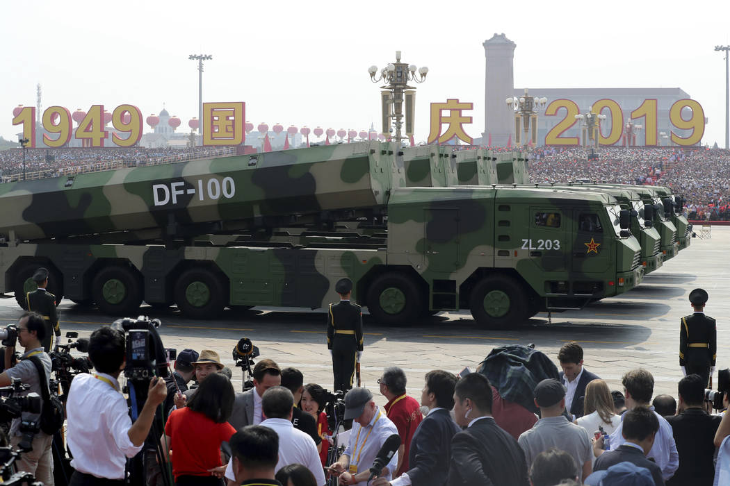 Military vehicles carrying DF-100 roll down as members of a Chinese military honor guard march ...