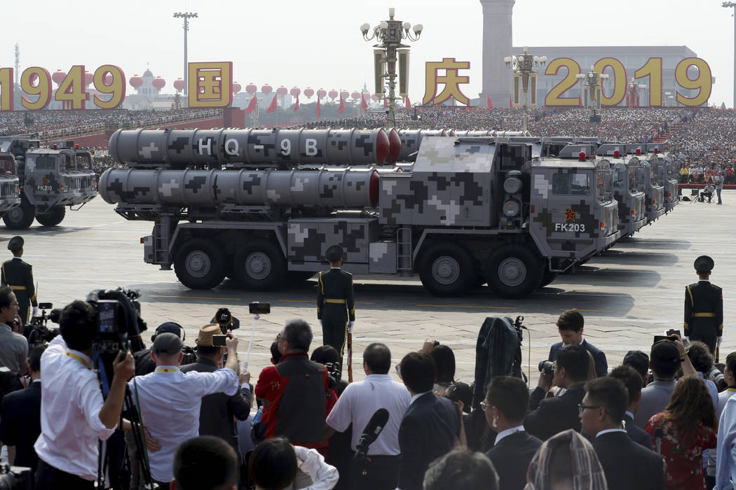 Military vehicles roll down as members of a Chinese military honor guard march during the parad ...
