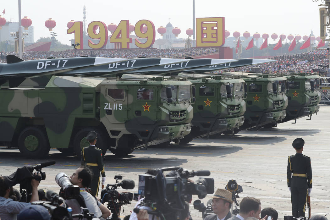 Military vehicles, carrying DF-17, roll down as members of a Chinese military honor guard march ...
