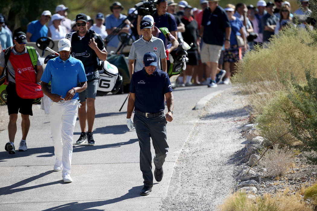 Phil Mickelson, right, Tony Finau and Kevin Na, behind Mickelson, walk the sixth hole during Sh ...