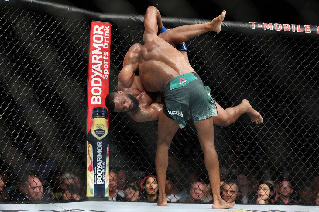 Kamaru Usman takes down Tyron Woodley in the welterweight title bout during UFC 235 at T-Mobile ...