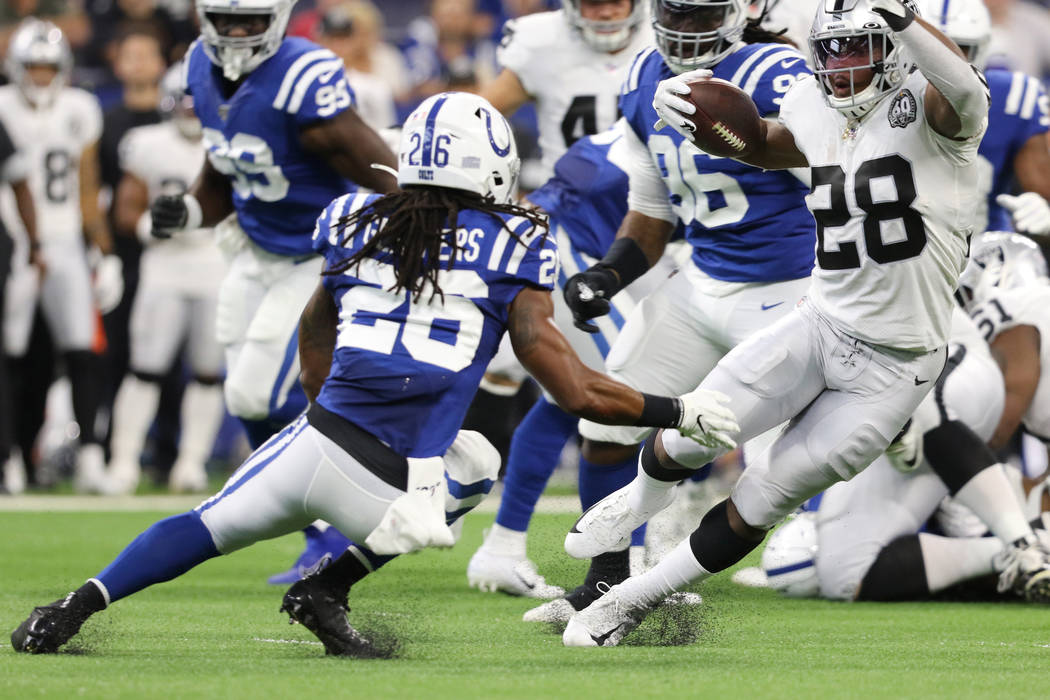 Oakland Raiders running back Josh Jacobs (28) runs past Indianapolis Colts strong safety Clayto ...