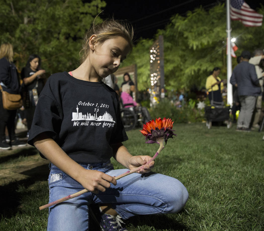 Ella Goldy holds a red sunflower honoring her mother Samantha Olander, who survived the Route 9 ...