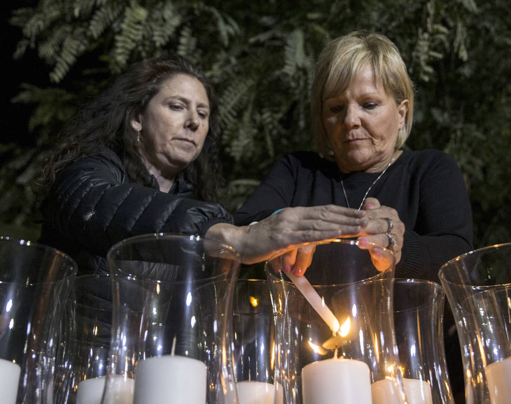 Mauricia Baca, left, and Esther Reinecke light candles honoring the 58 victims of the Route 91 ...