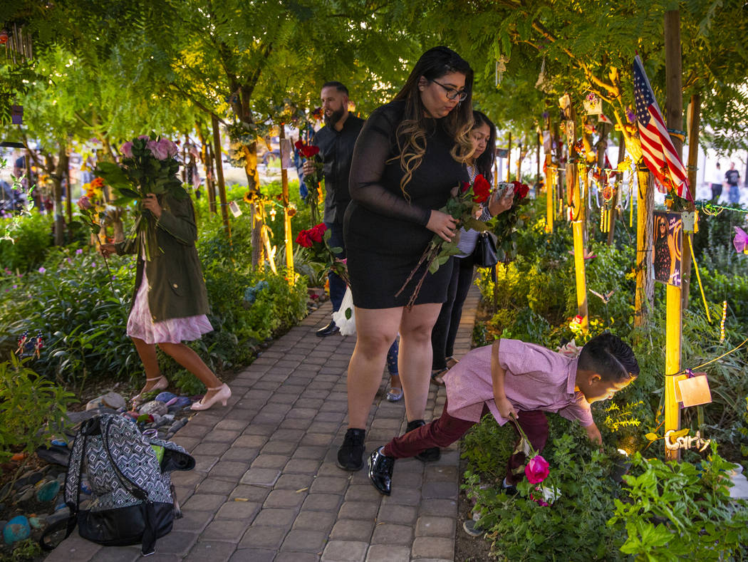The King family lays flowers for each October 1st victim along the path of decorated trees at ...