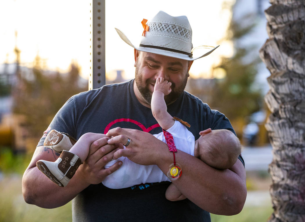 October 1st survivor Gerald Crisp plays with his son Colby, 4 month-old, while visiting the Las ...
