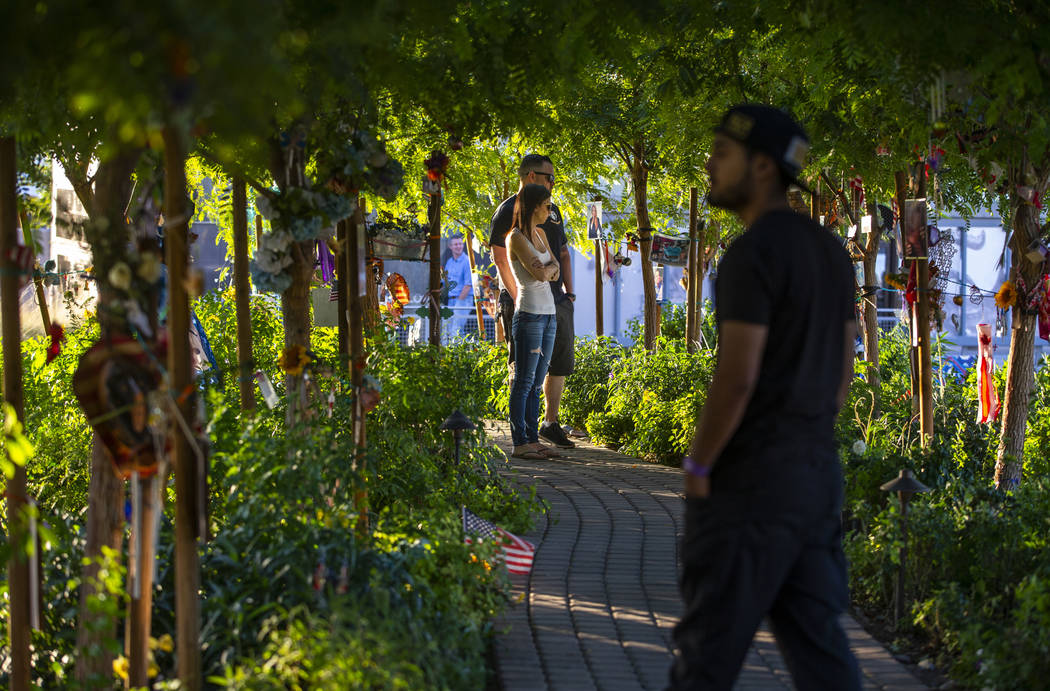 Visitors walk along the path of decorated trees at the Las Vegas Healing Garden on Tuesday, Oct ...