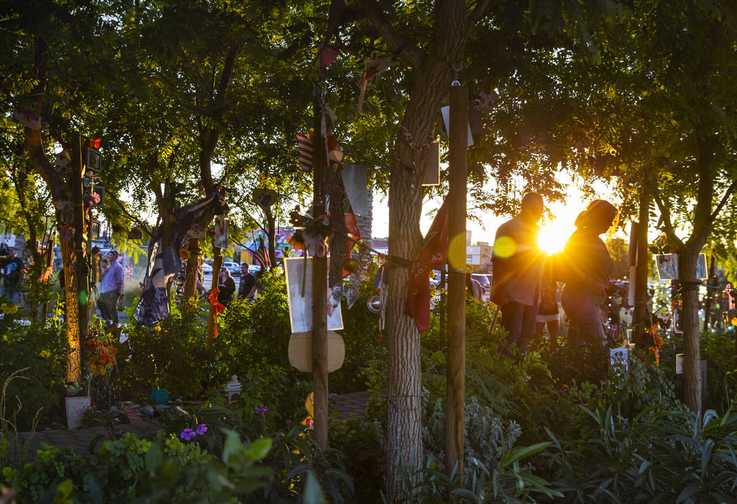 The sun begins to set as visitors walk along the path of decorated trees at the Las Vegas Heali ...