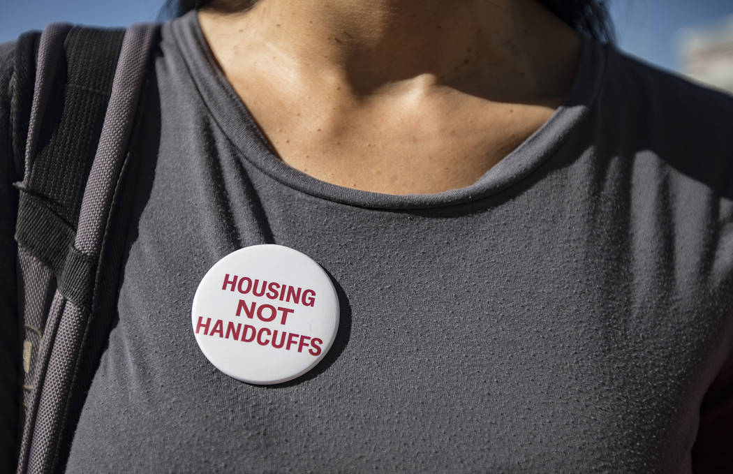 Merideth Spriggs, founder of the nonprofit Caridad, wears a button in protest against a propose ...
