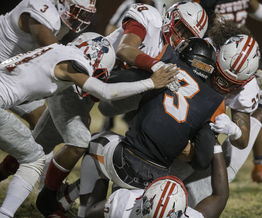 Chaparral senior running back Meshach Hawkins (3) is stacked up by a gang of Liberty defenders ...