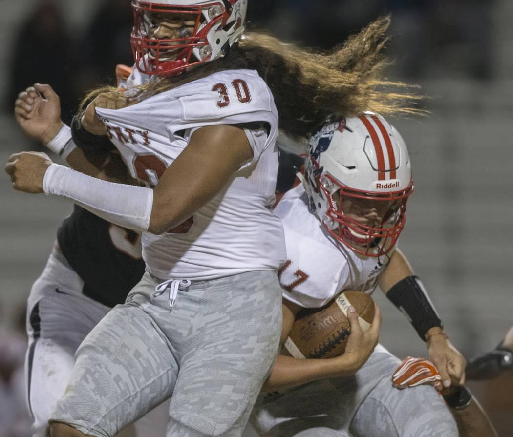 Liberty sophomore quarterback Katin Houser (17) collides with junior running back Zyrus Fiaseu ...