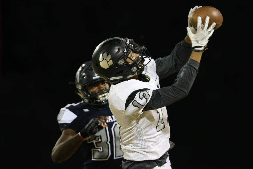Palo Verde's Jahan Wright (13) makes a catch under pressure from Shadow Ridge's Dural Faust (30 ...