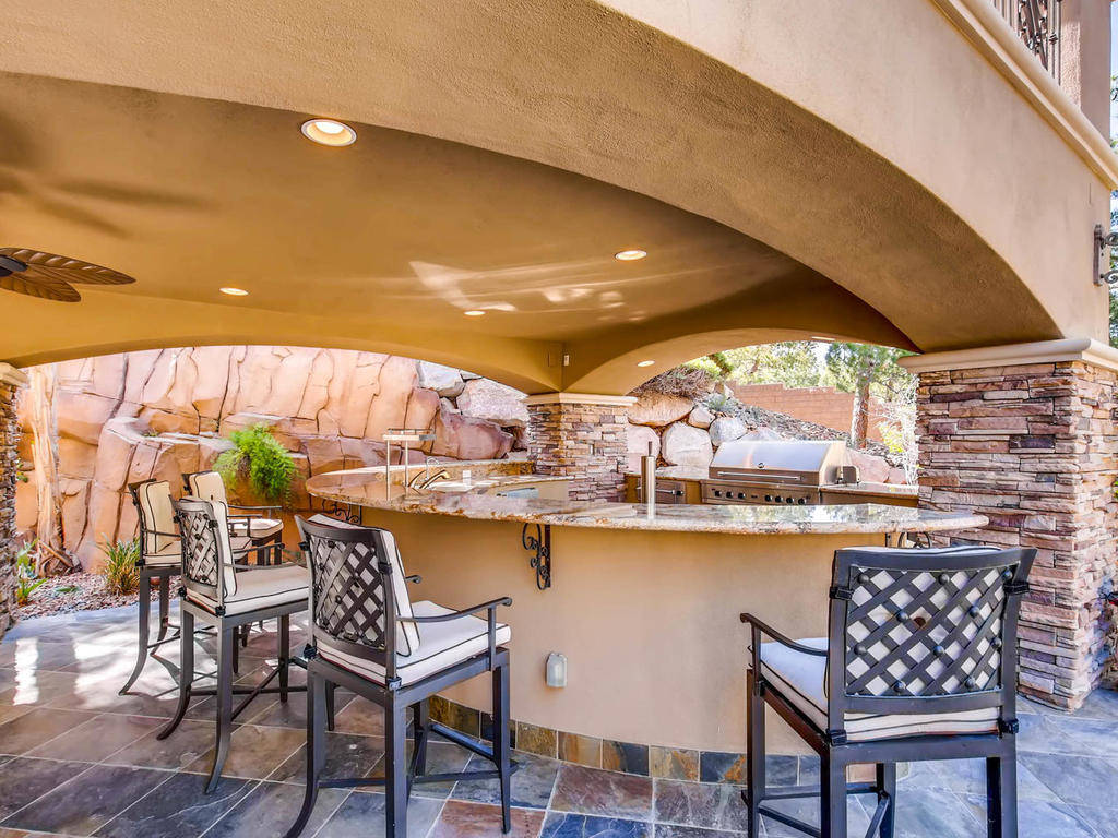 The outdoor kitchen has a bar with seating.