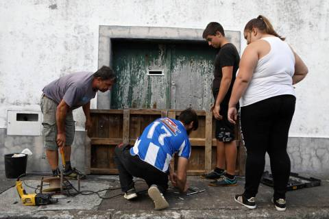 Residents board up a door in preparation for the arrival of hurricane Lorenzo in Horta, the cap ...