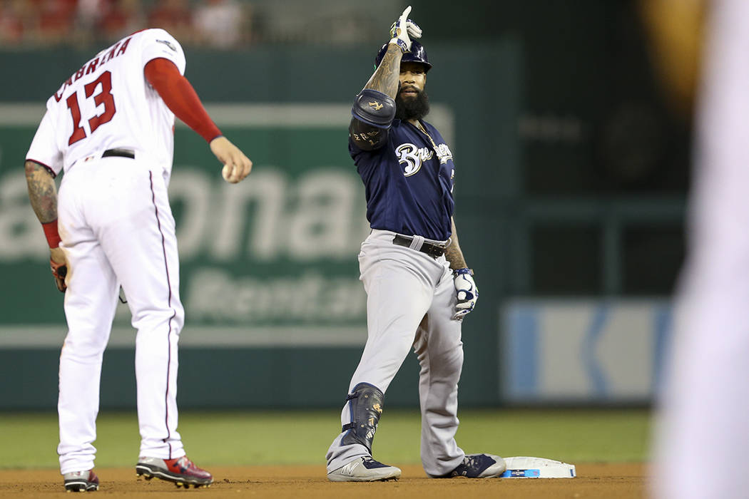 Milwaukee Brewers' Eric Thames, center, gestures to his teammate after hitting a double during ...